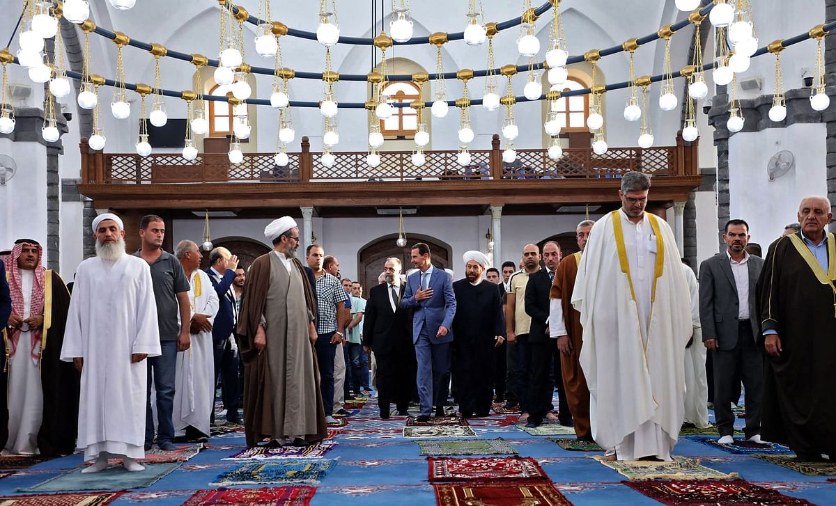 A handout picture released by the official Facebook page of the Syrian Presidency shows President Bashar al-Assad (C) performing Eid al-Adha prayer at Khaled bin al-Walid mosque in Homs on July 20, 2021.