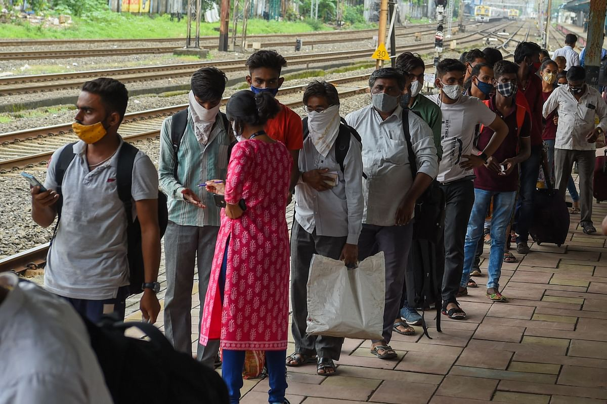 Passengers queue up to test for the Covid-19 coronavirus after arriving at a railway platform on a long distance train in Mumbai on July 9, 2021.