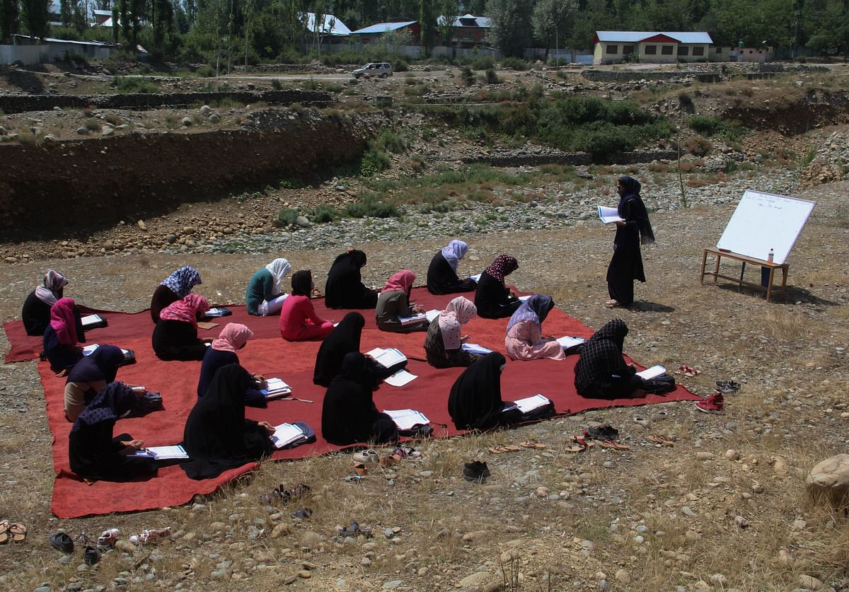 A teacher teaches students during an open-air class while wearing protective face masks and maintaining social-distancing norms amid the Covid-19 pandemic on the outskirts of Srinagar, Jammu & Kashmir.