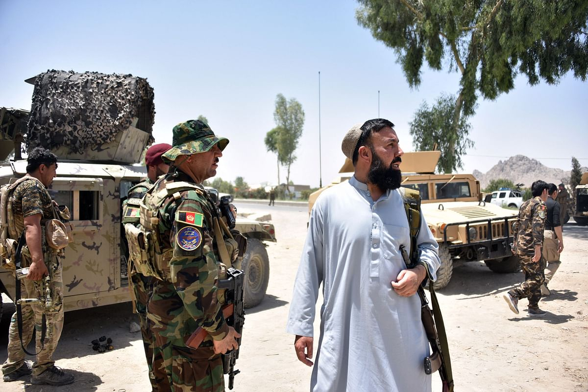 Afghan security personnel stand guard along the road amid ongoing fight between Afghan security forces and Taliban fighters.