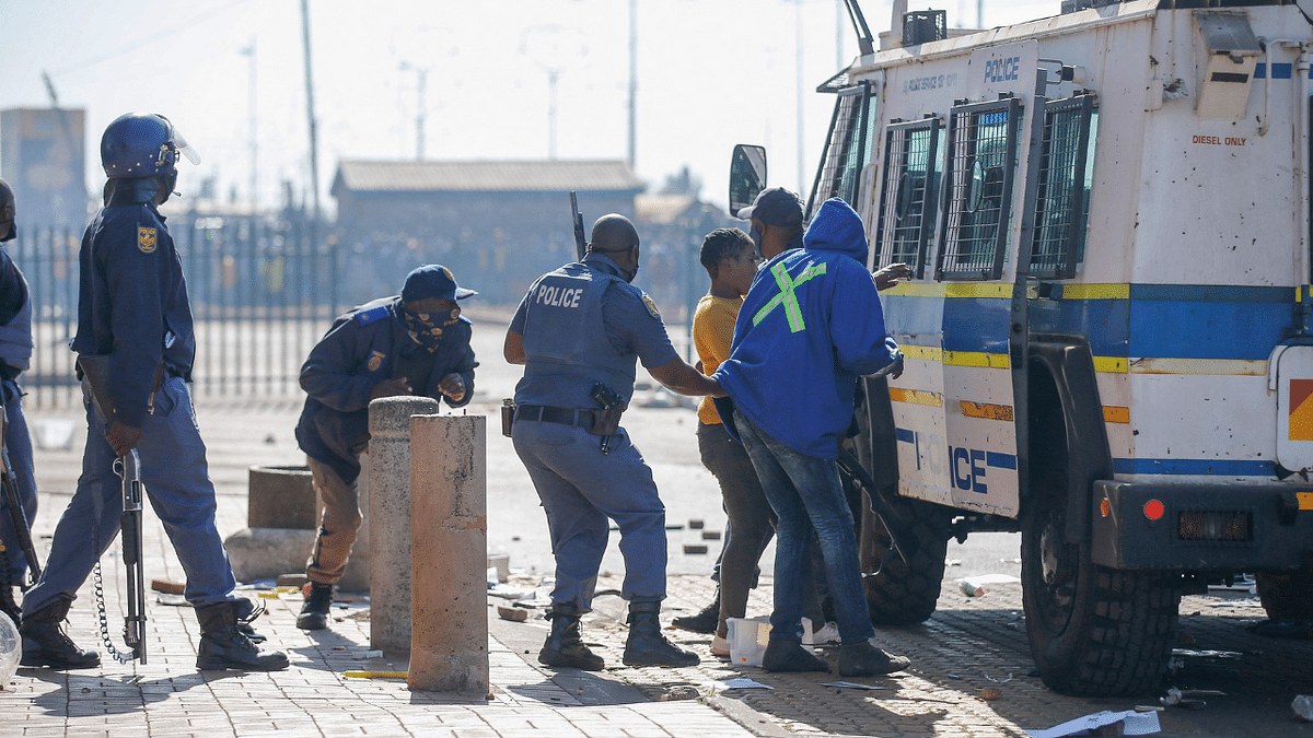 Members of the South African Police Services (SAPS) arresst suspected looters following sporadic looting and vandalism outside the Lotsoho Mall in Katlehong township, East of Johannesburg, on July 12, 2021.