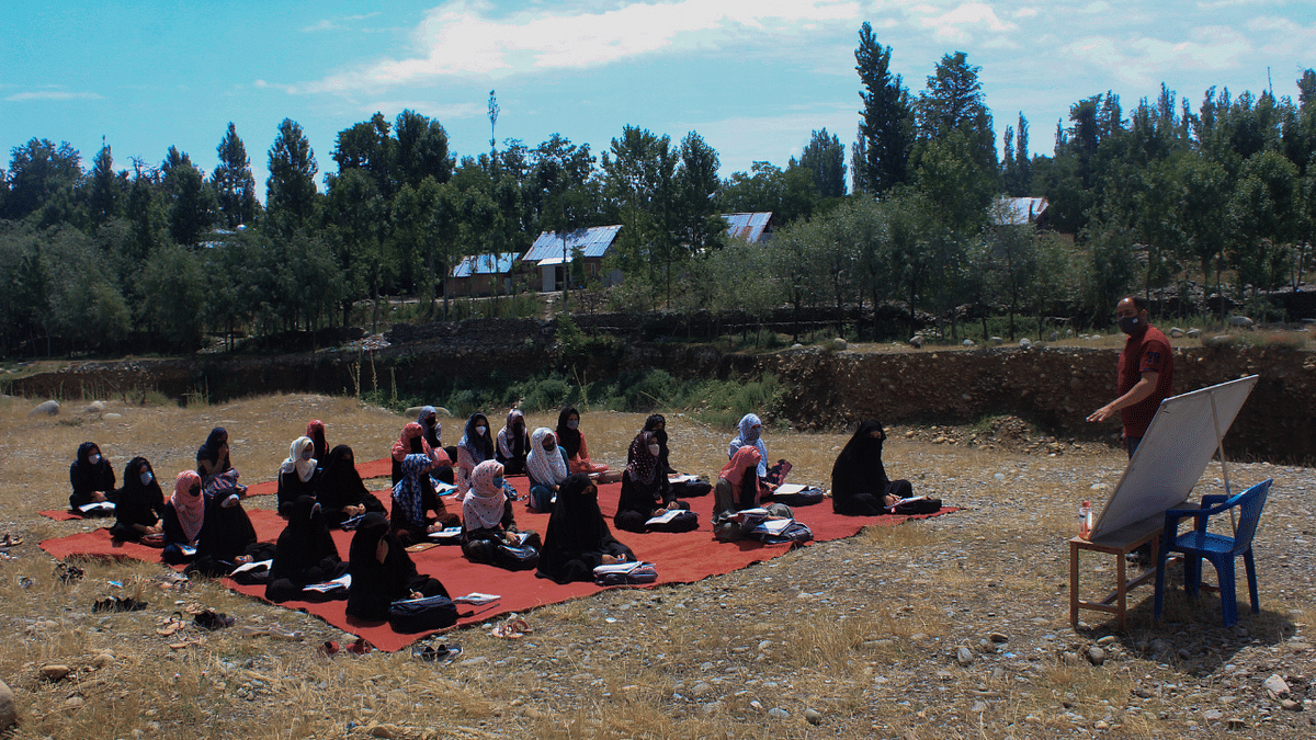 Kashmiri students attend open-air class wearing protective face masks to maintain social-distancing norms amid the Covid-19 pandemic on the outskirts of Srinagar, Jammu & Kashmir.