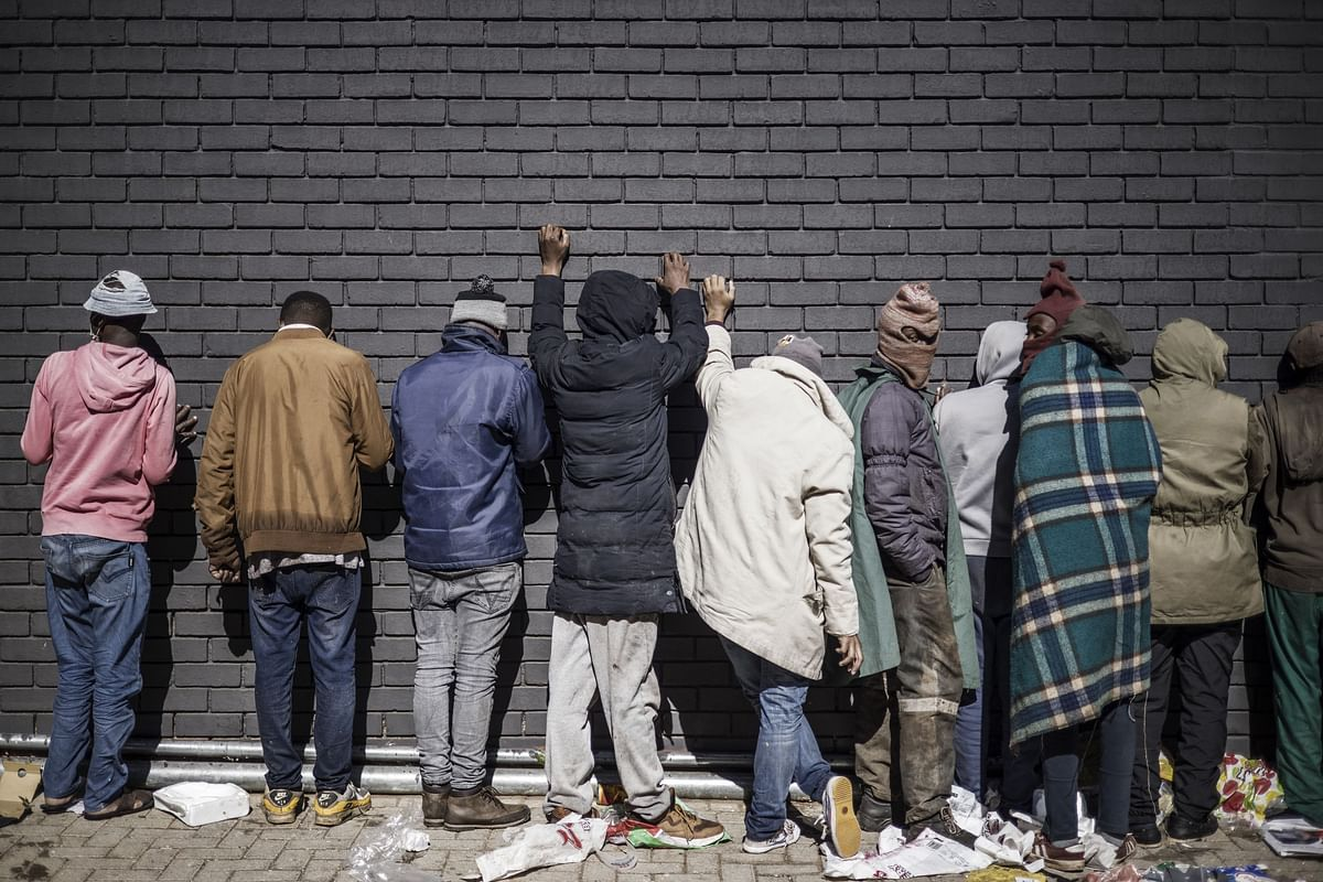 Suspected looters, rounded up by the South Africa police Services (SAPS) and local private security officers lean against a wall after being caught red handed and detained in Vosloorus, on July 13, 2021.