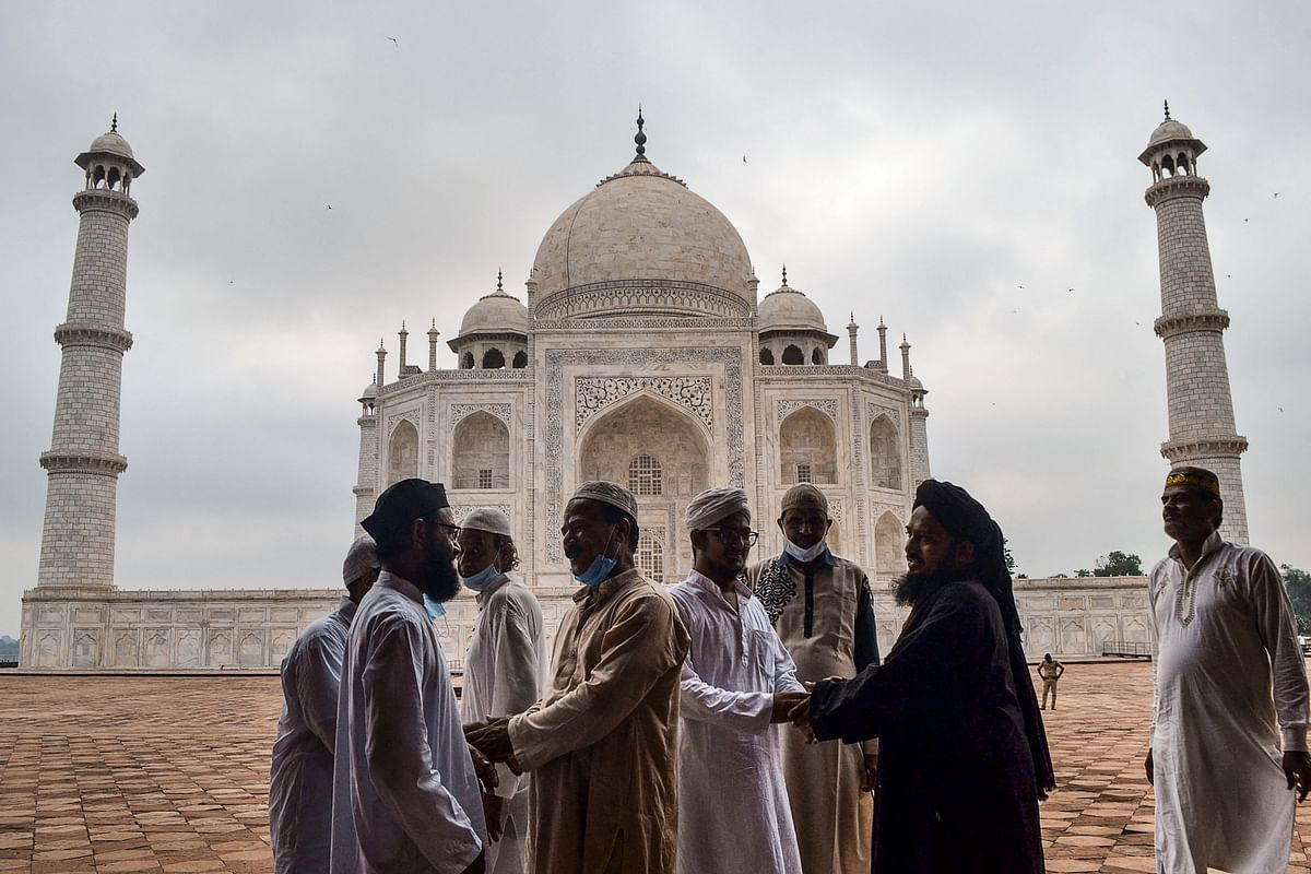 Muslim devotees greet as they arrive to offer prayers to mark the start of the Muslim festival Eid al-Adha or the Festival of Sacrifice, at the Taj Mahal in Agra on July 21, 2021.