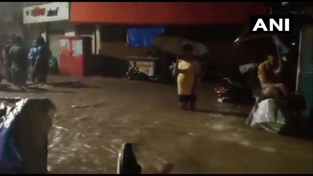 People wadding through waterlogged streets in Kandivali