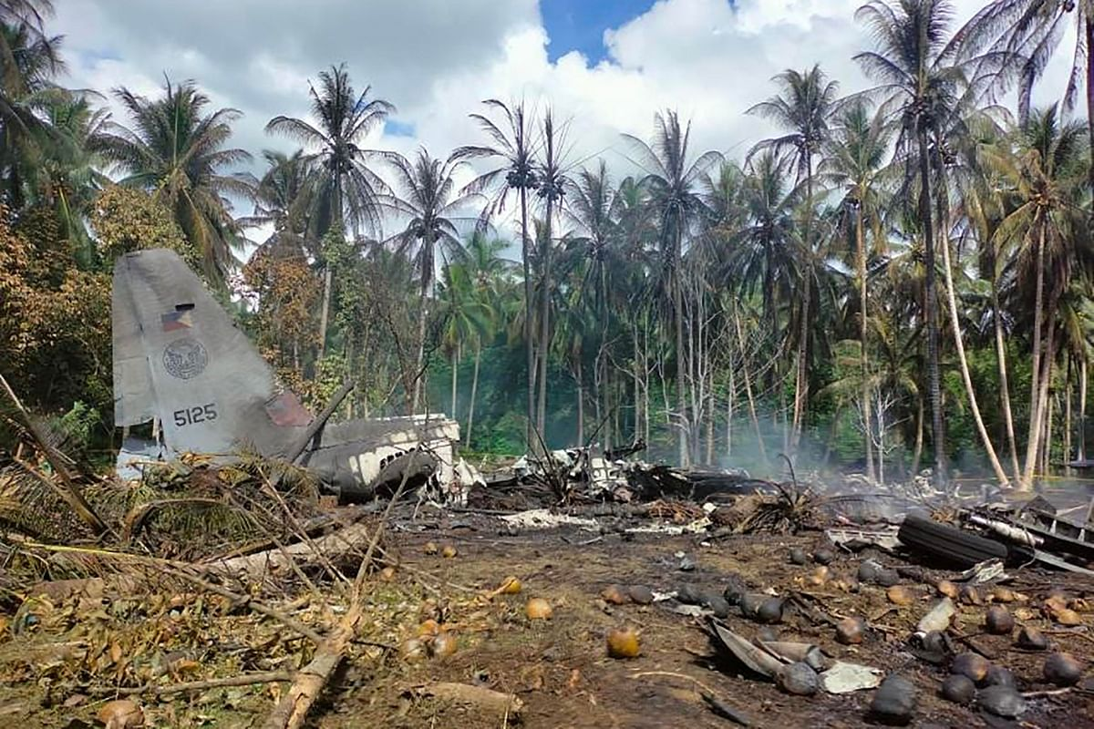 n this handout photo taken on July 4, 2021 and received from the Philippine military Joint Task Force-Sulu (JTF-Sulu), smoke billows from the wreckage of a Philippine Airforce C-130 transport plane after it crashed near the airport in Jolo town, Sulu province on the southern island of Mindanao.