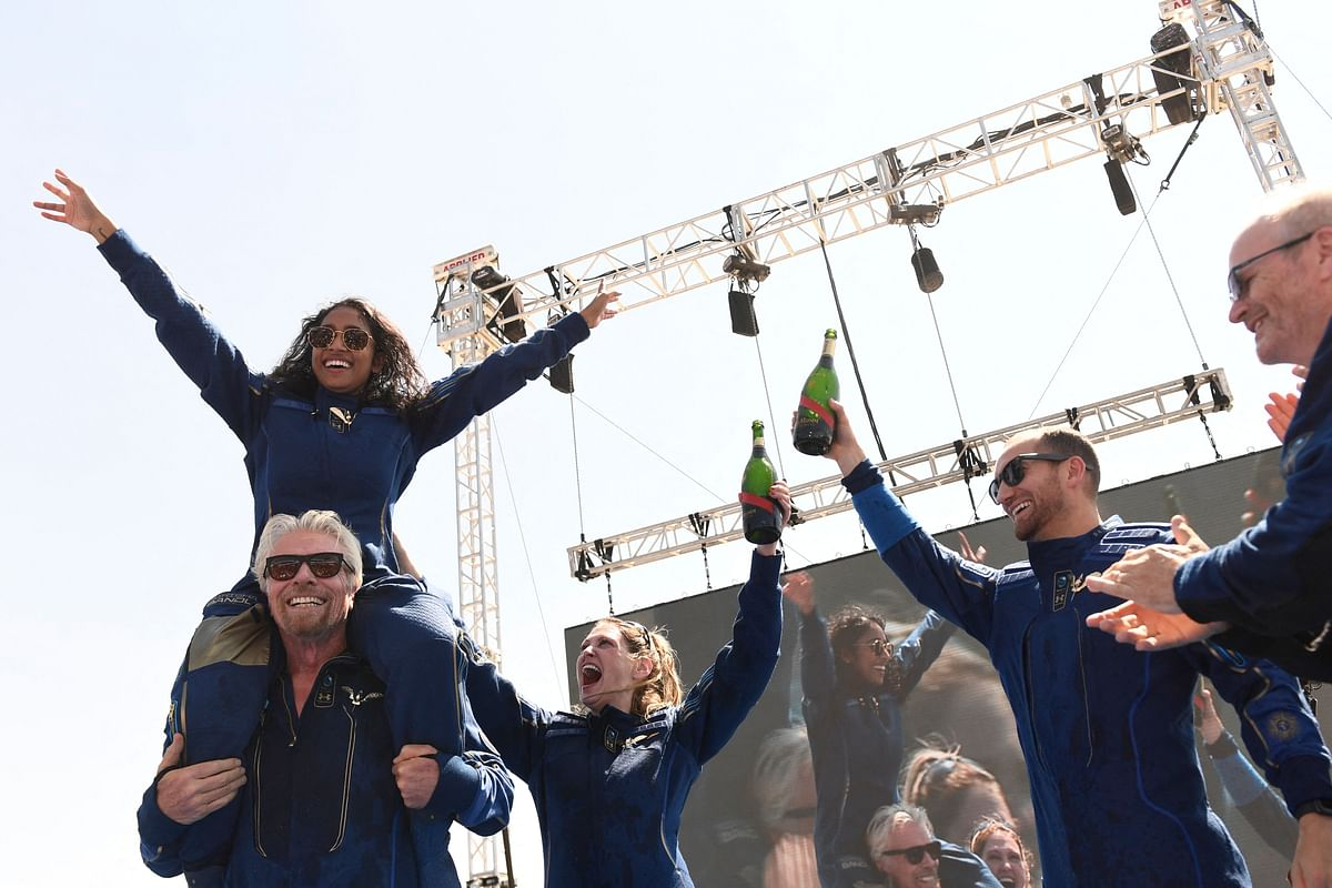 Virgin Galactic founder Sir Richard Branson(L), with Sirisha Bandla on his shoulders, cheers with crew members after flying into space aboard a Virgin Galactic vessel.