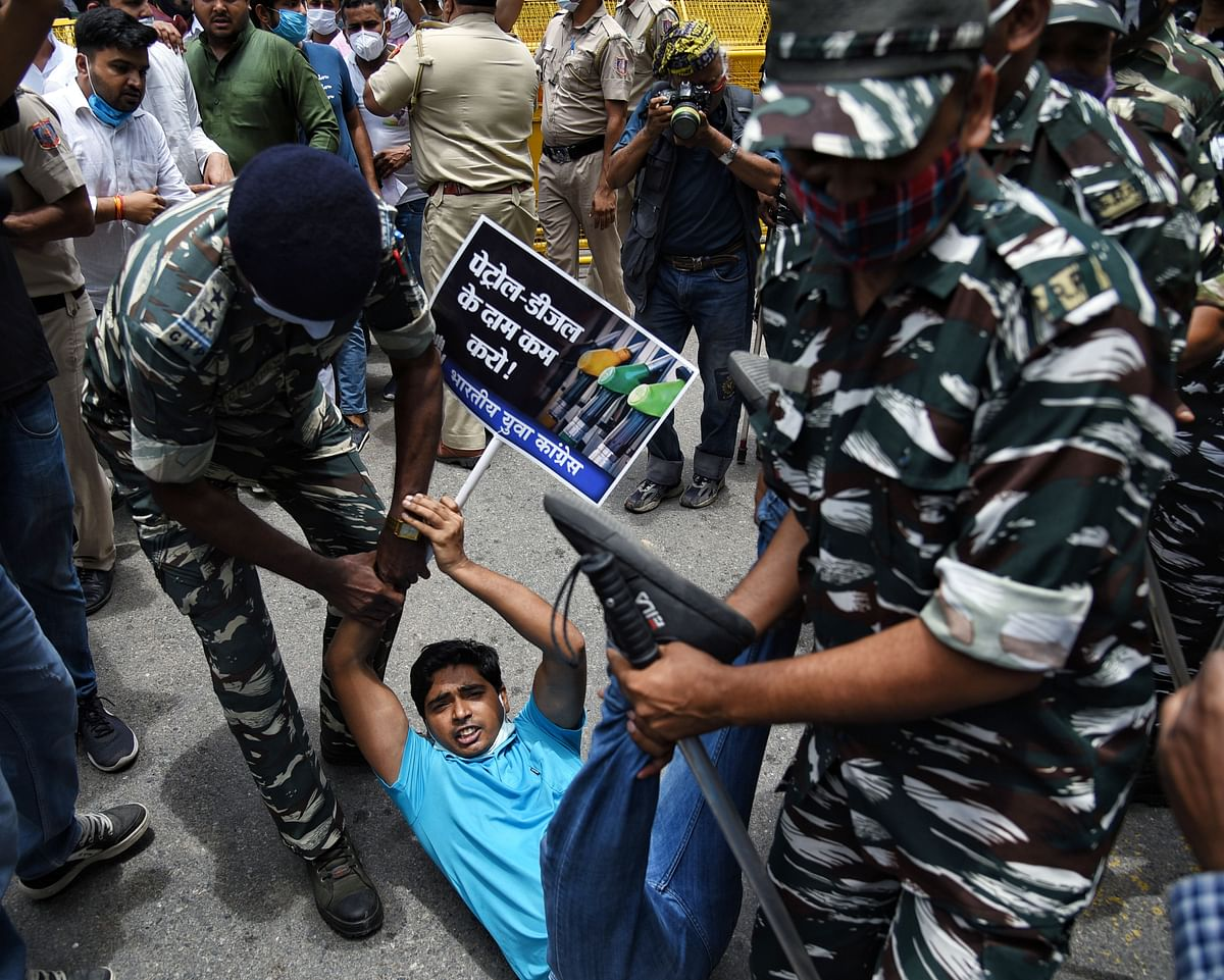 Security personnel detain the supporters of Indian Youth Congress (IYC) during a protest against the hike in fuel prices outside Shastri Bhawan, in New Delhi on Saturday.