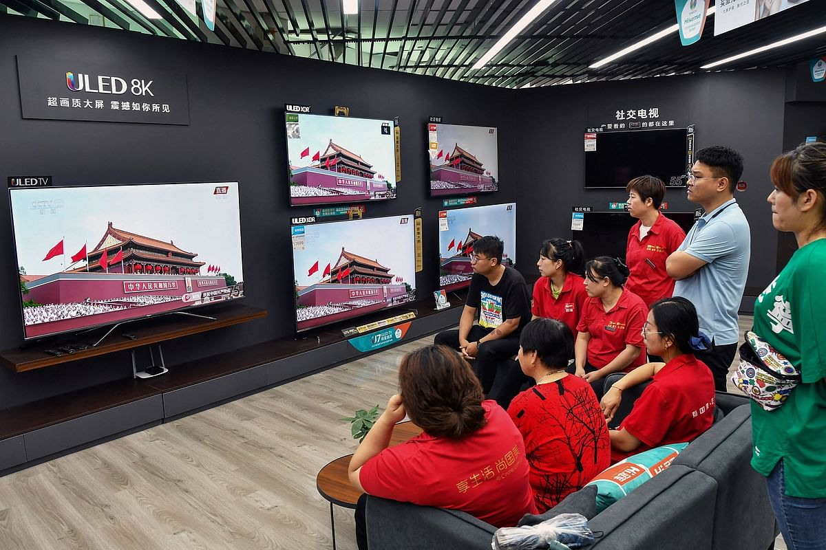 Staff members and customers watch a television showing the celebrations to mark the 100th anniversary of the founding of the Communist Party of China at a shopping mall in Yantai, in Chinas eastern Shandong province on July 1, 2021.