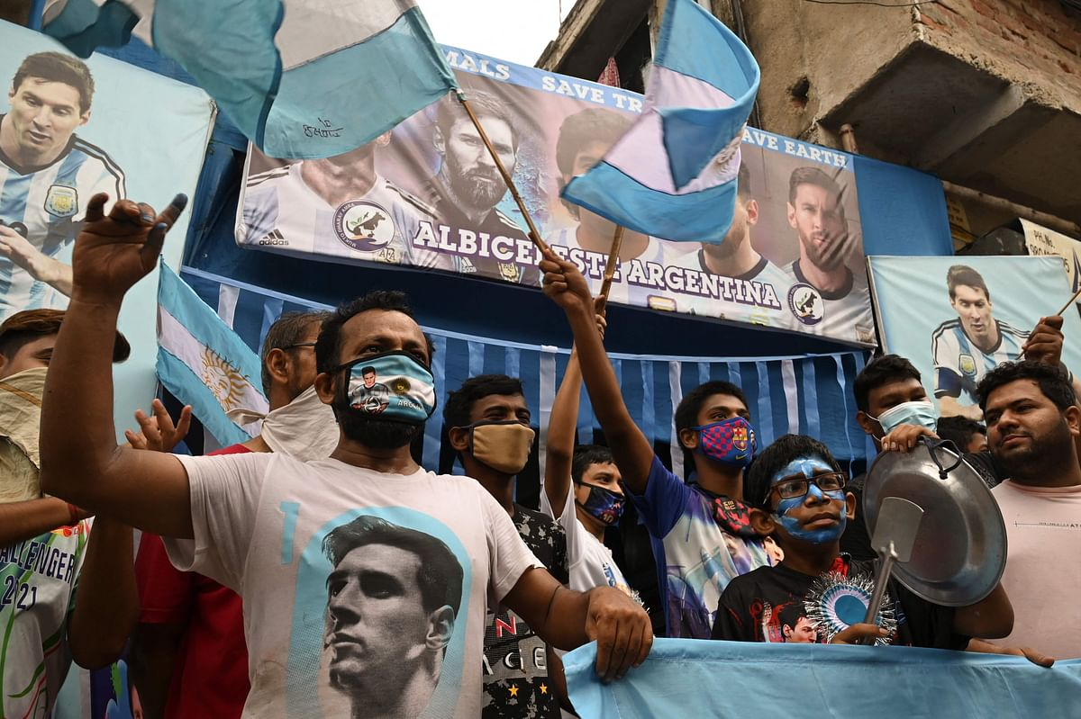 Argentina football fans hold national flags as they celebrate after winning the Conmebol 2021 Copa America football tournament final match against Brazil, in Kolkata on July 11, 2021.