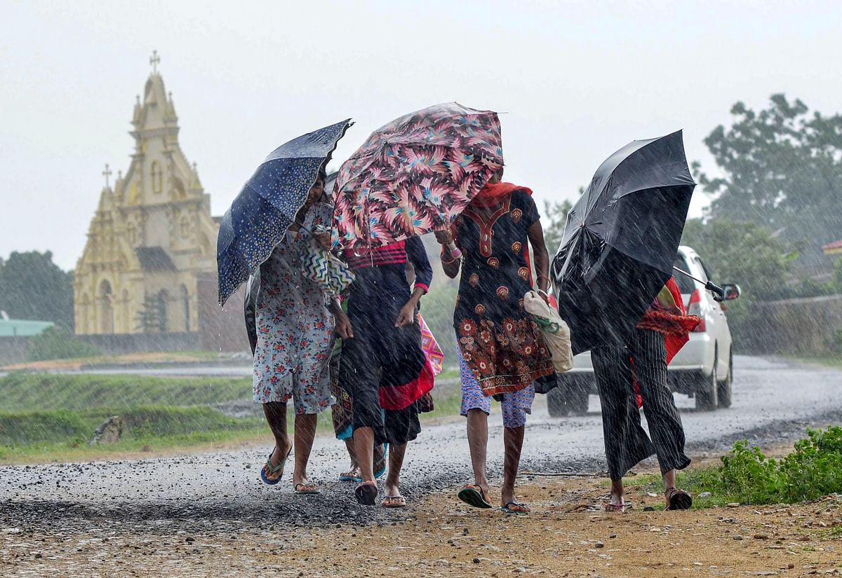 Pedestrians carrying umbrellas, cross a street amid rain in Ranchi, Friday, July 2, 2021.