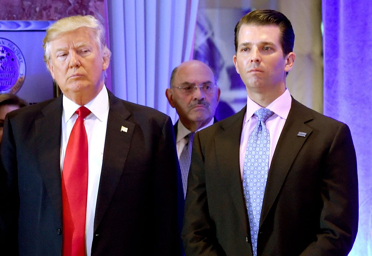 Donald Trump along with his son Donald, Jr., arrive for a press conference at Trump Tower in New York in 2017, as Allen Weisselberg (C), chief financial officer of The Trump, looks on