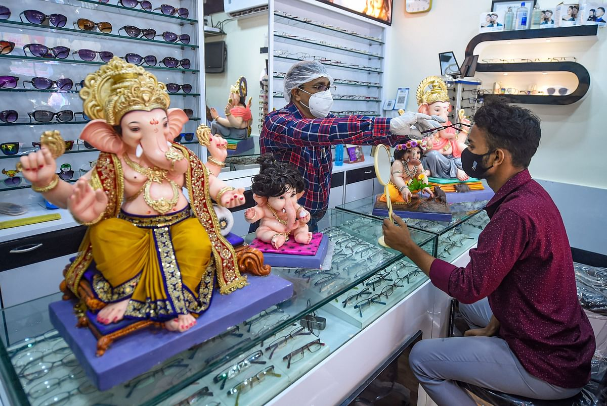 Mumbai: An optician attends a customer during COVID-19 pandemic, in Mumbai, Thursday, July 1, 2021. He also sells Ganpati idols that he purchased from Pen ahead of Ganesh Chaturthi festival.