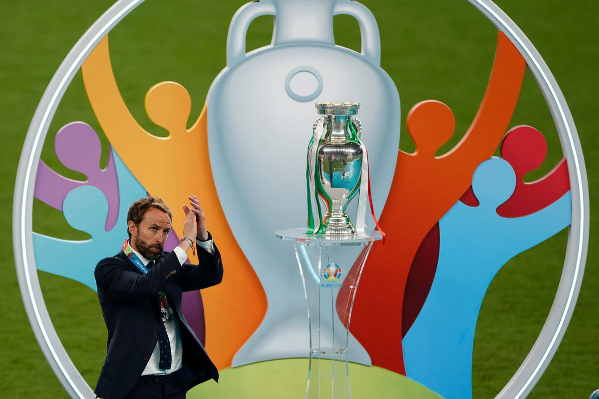 England coach Gareth Southgate greets the fans as he walks past the trophy during the UEFA EURO 2020 final football match between Italy and England at the Wembley Stadium in London on July 11, 2021.