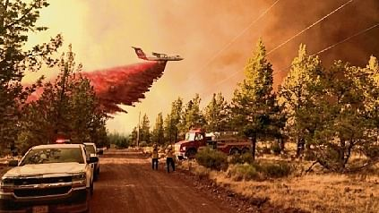 A firefighting tanker makes a retardant drop over the Grandview Fire near Sisters, Oregon, US.
