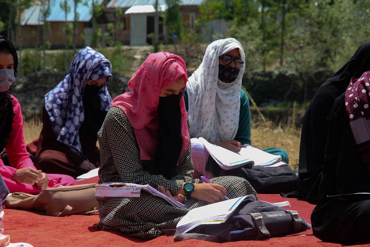 Kashmiri students study in an open-air class wearing face masks following Covid-19 guidelines and social-distancing norms amid the pandemic on the outskirts of Srinagar, Jammu & Kashmir.