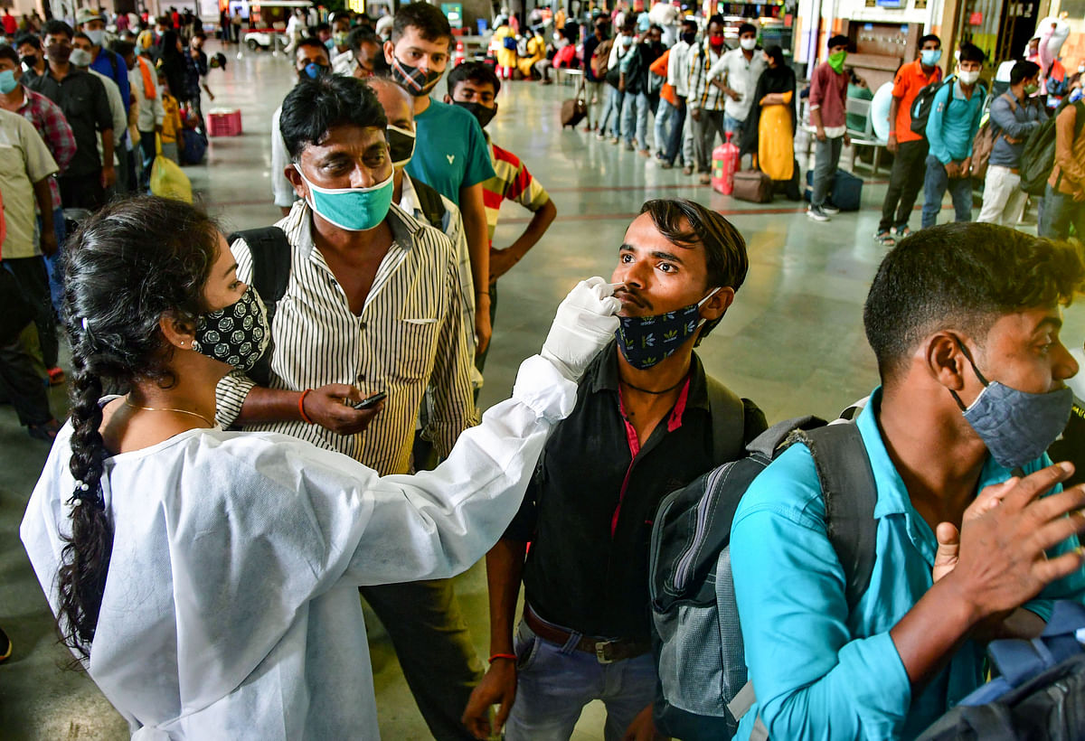 Mumbai: A BMC health worker collects swab sample of a passenger for COVID-19 test, at the CSMT station, in Mumbai, Wednesday, July 14, 2021.