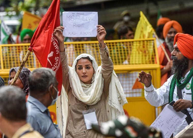 Actress Sonia Mann along with farmers hold placards at Kisan Sansad during a protest against the three farm laws at Jantar Mantar, in New Delhi on Thursday.