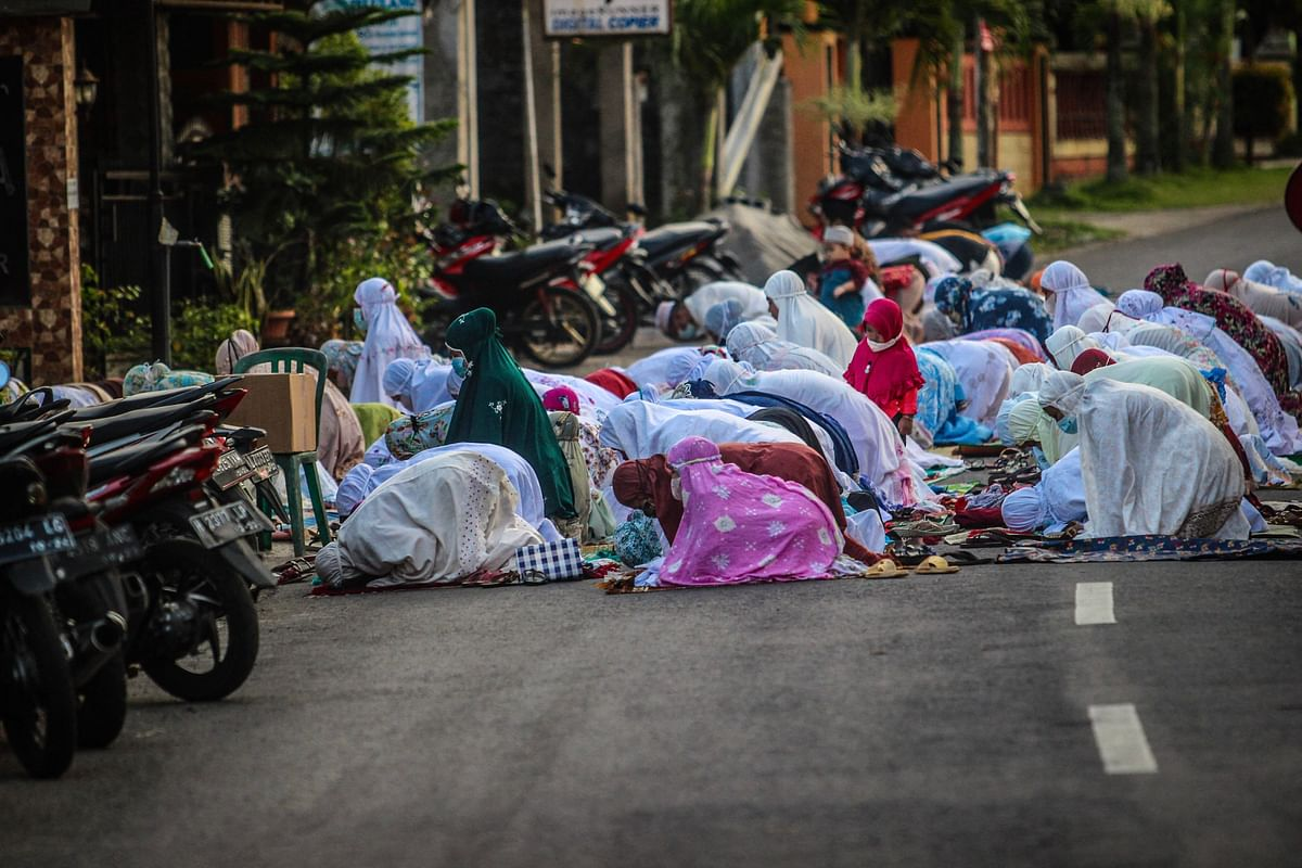 Muslims gather on the road to pray outside a mosque to mark Eid al-Adha, the annual celebration known as the Festival of Sacrifice, in Ungaran, Central Java on July 20, 2021.