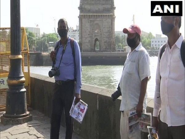 Photographers wait for tourists near Gateway of India
