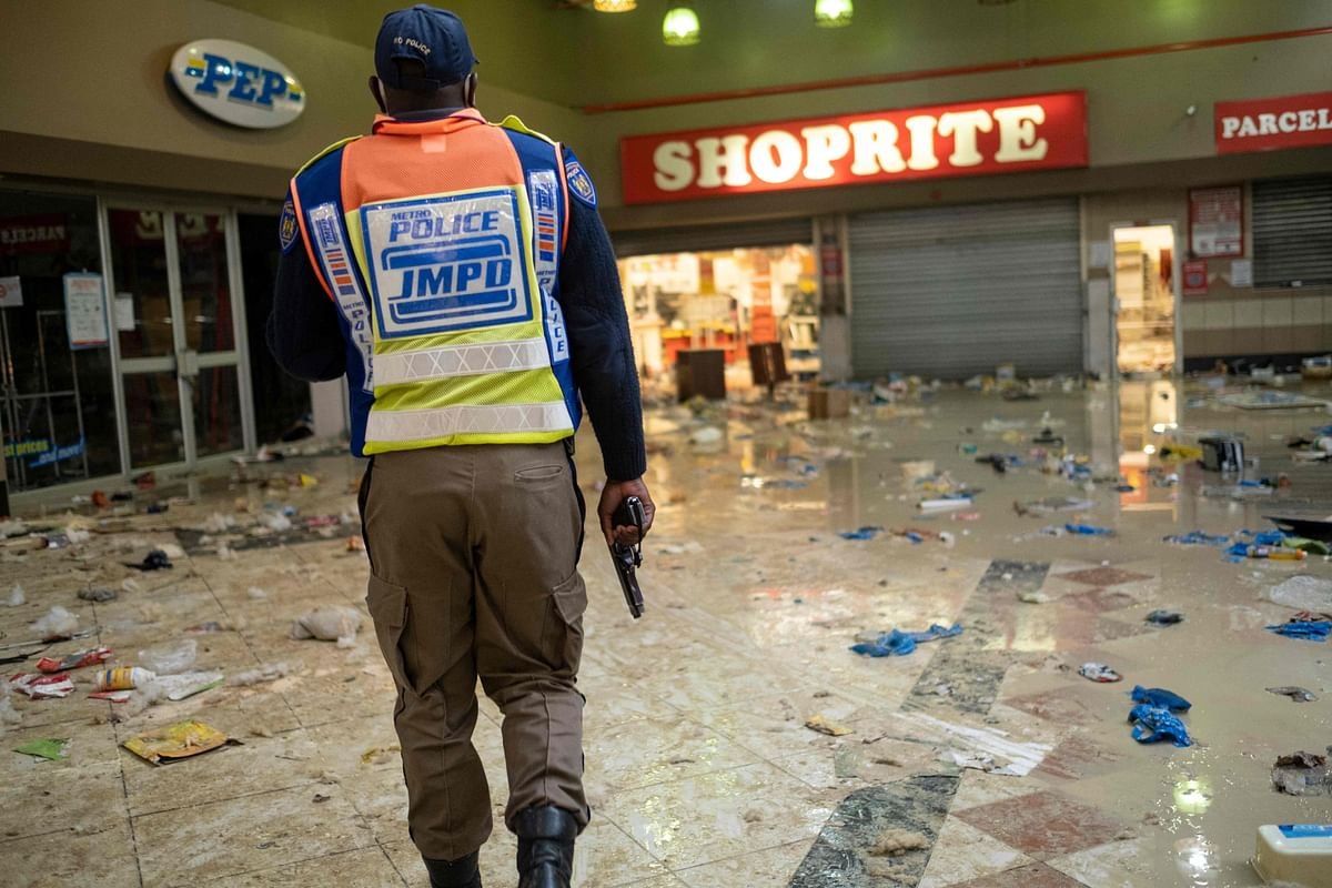 Johannesburg Metro Police Department (JMPD) officer carries his firearm while searching for looters at the Bara Mall in Soweto on the outskirts of Johannesburg on July 13, 2021