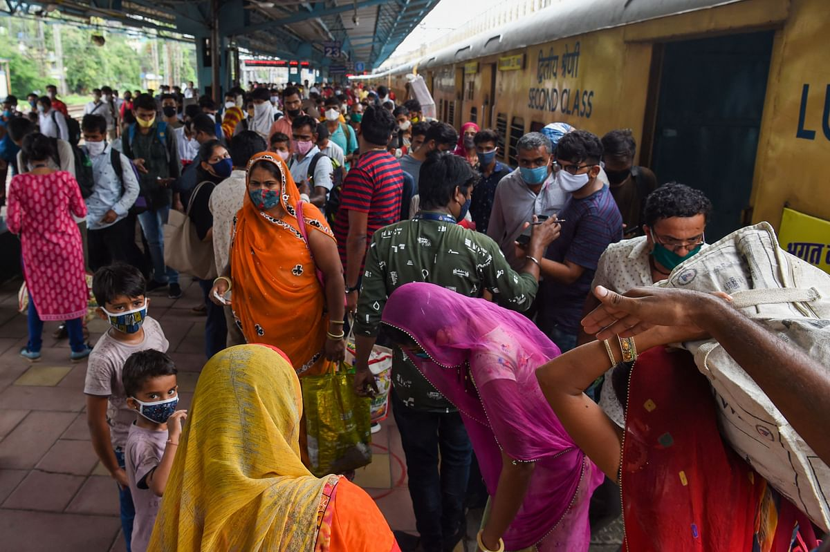 Passengers crowd as they prepare to queue up for the Covid-19 coronavirus test after arriving at a railway platform on a long distance train in Mumbai on July 9, 2021.