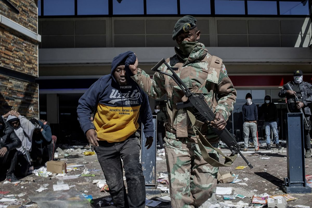 A South Africa National Defence Force (SANDF) soldier detains a suspected looter at Jabulani Mall in Soweto on July 13, 2021.