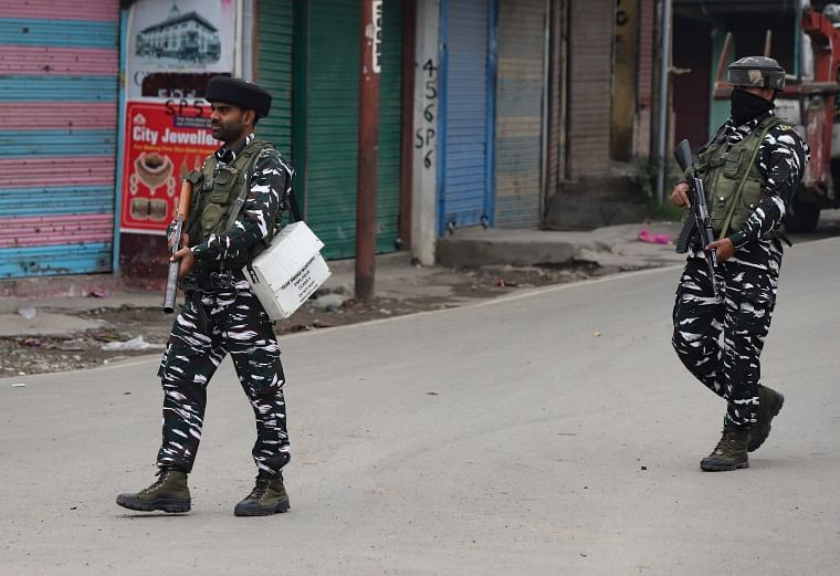 Policemen stand guard on an armored vehicle as they move towards the site of a gunfight in Pulwama town