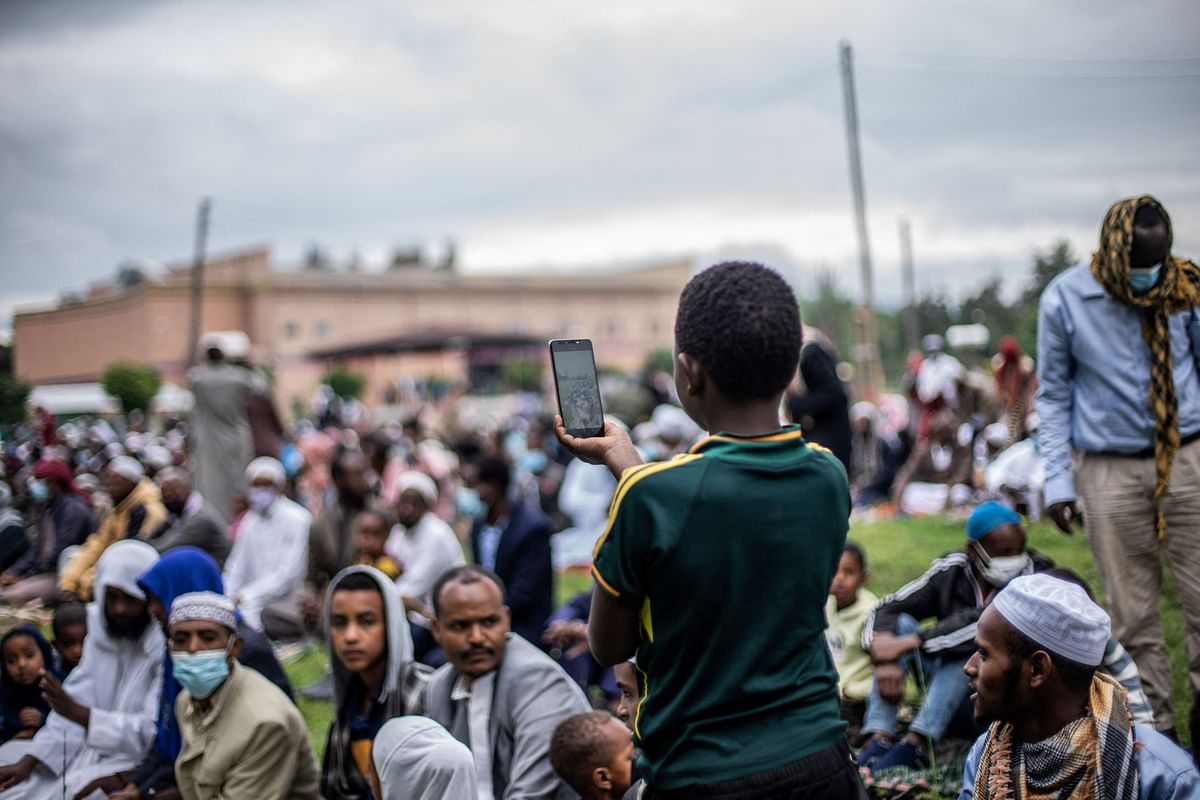 A muslim boy takes pictures during the Eid al-Adha prayers on the first day of the feast celebrated by Muslims worldwide, at the Millennium Square in Hawassa, Ethiopia, on July 20, 2021.