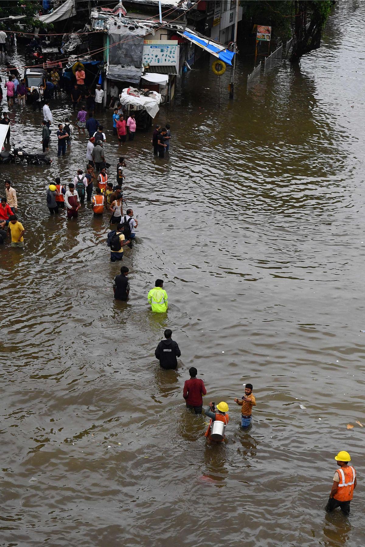 People wade along a waterlogged street following a heavy monsoon rainfall in Mumbai on July 16, 2021.