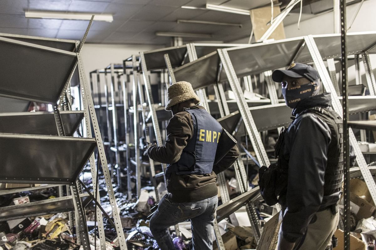 South Africa police officers inspect the damages at a looted mall in Vosloorus, on July 13, 2021.