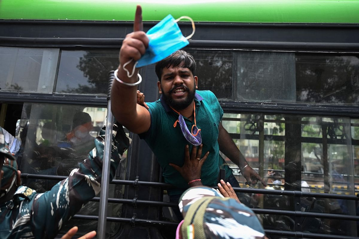 An activist of the Indian Youth Congress (IYC) party shouts slogans after being detained by police during a protest against the recent price hike of fuel and Liquefied Petroleum Gas (LPG) cylinder, outside the ministry of petroleum and natural gas in New Delhi on July 3, 2021