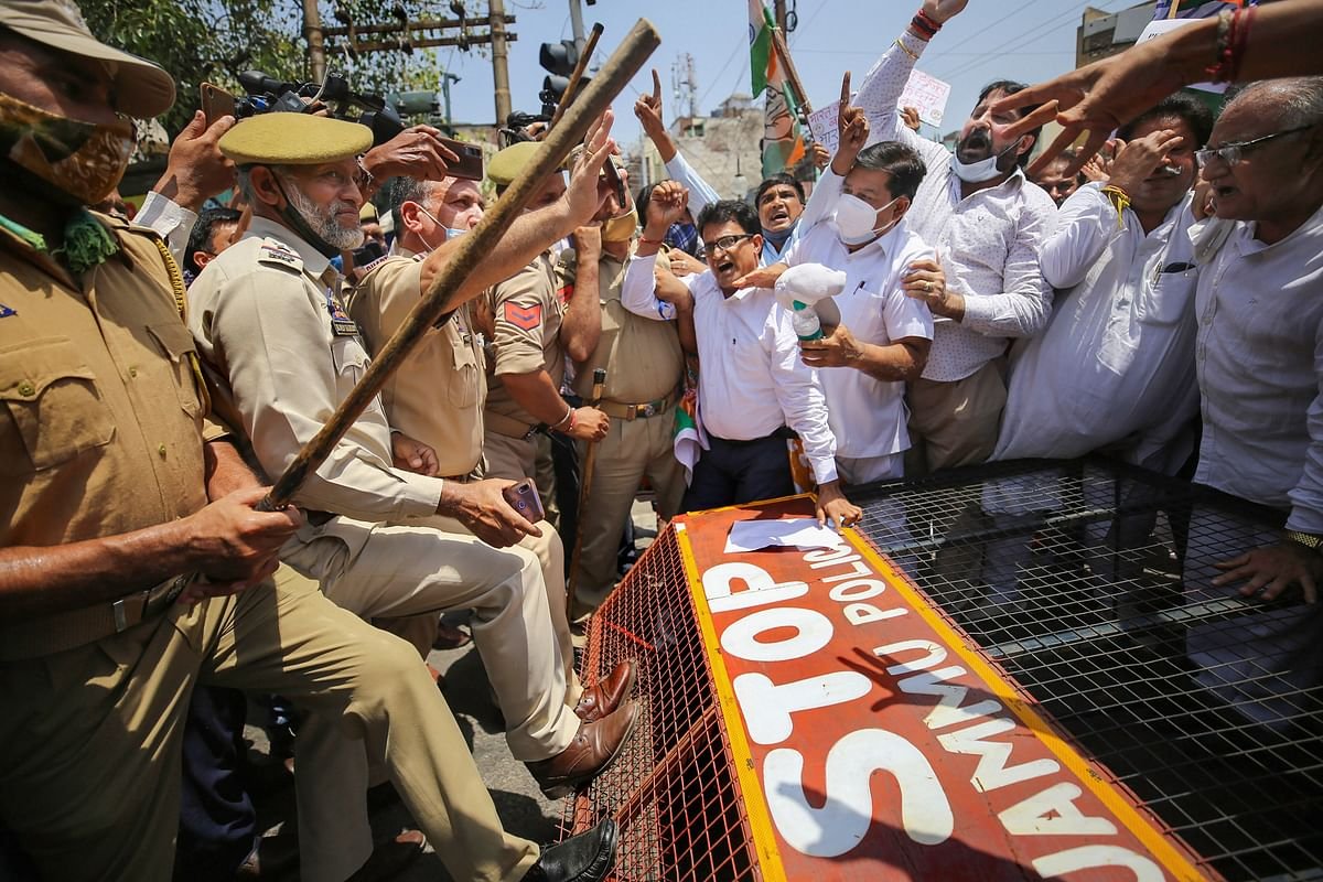 Police stop Congress workers who were staging a protest demanding for restoration of statehood to J & K, and against hike in the fuel prices, in Jammu, Wednesday, July 7, 2021.