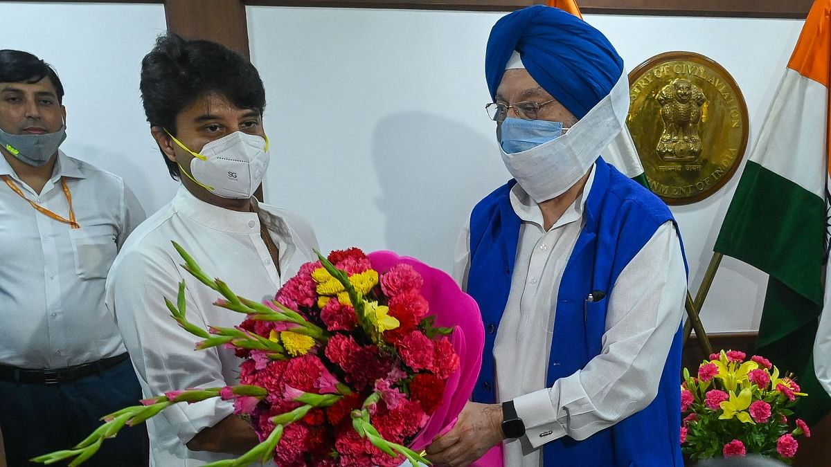 Outgoing Union civil aviation Minister Hardeep Singh Puri (R) presents a bouquet to new Union civil aviation Minister Jyotiraditya Scindia (L) after he arrived to take charge at Civil Aviation ministry in New Delhi