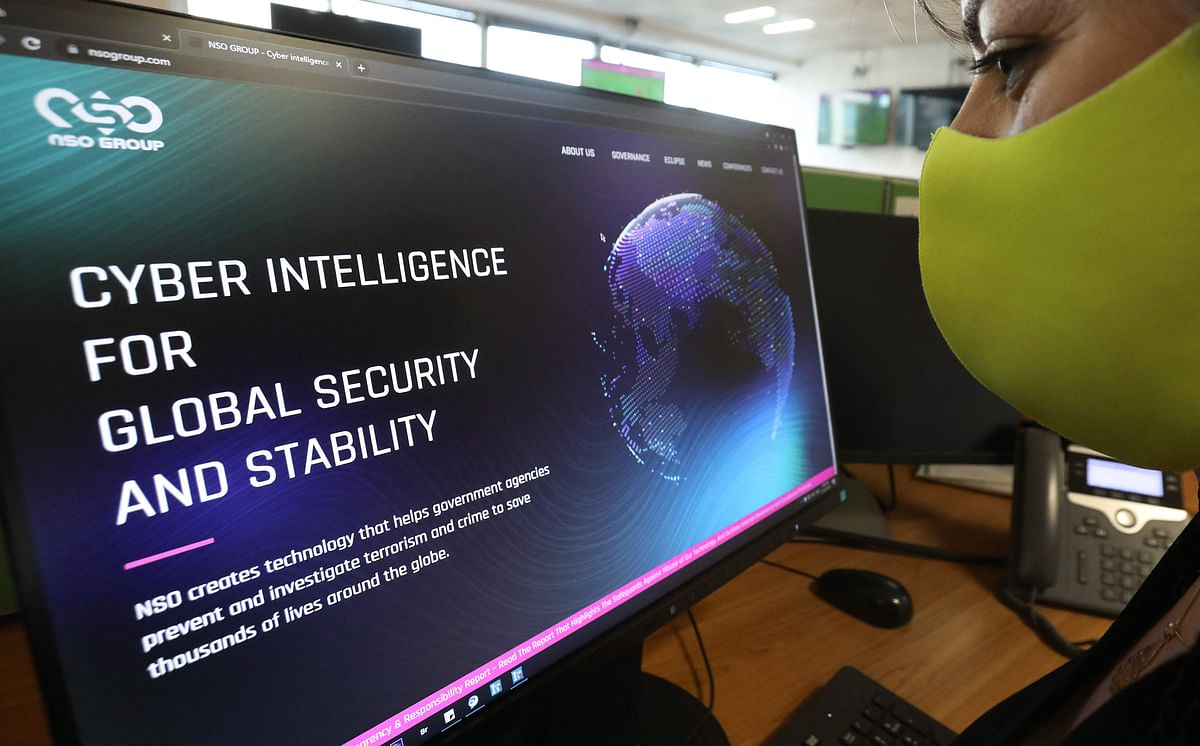 """A woman checks the website of Israel-made Pegasus spyware at an office in the Cypriot capital Nicosia on July 21, 2021. - Reports that Israel-made Pegasus spyware has been used to monitor activists, journalists and politicians around the world highlight the diplomatic risks of nurturing and exporting """"oppressive technology"""", experts warned."""