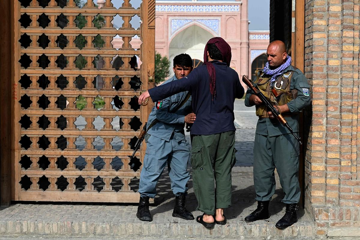 An Afghan security personnel frisks a devotee at the entrance of a mosque during the Eid al-Adha prayers in Kabul on July 20, 2021.