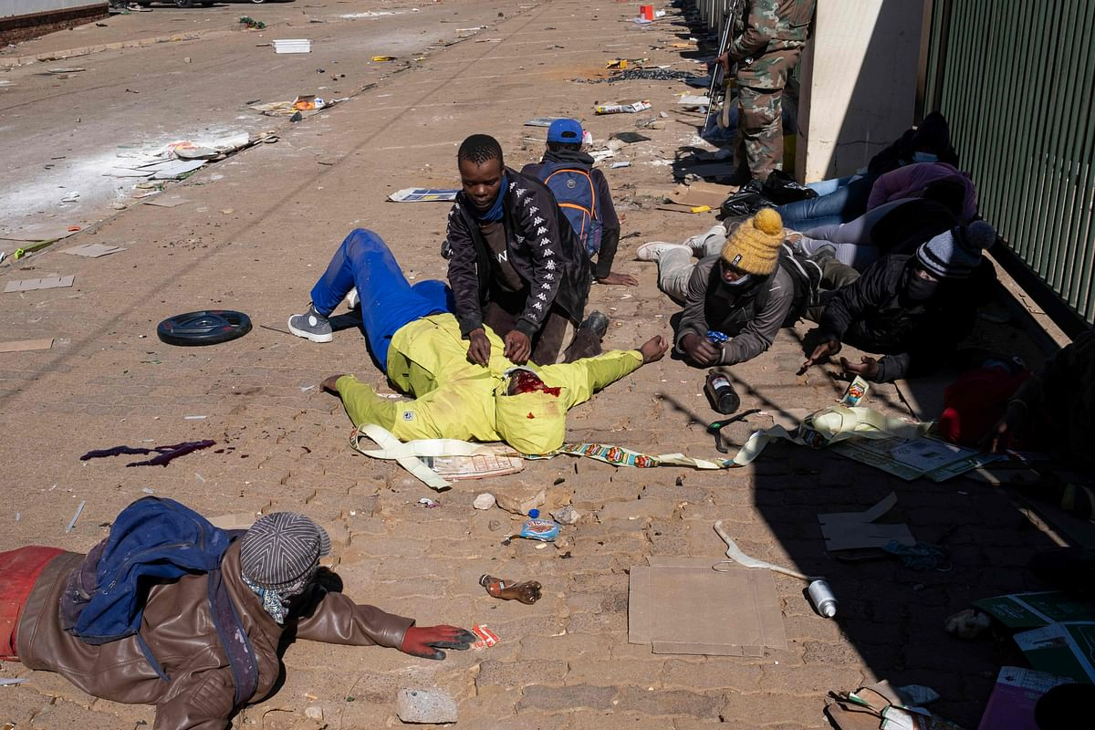 A suspected looter who was allegedly wounded by rubber bullets shot by Jabulani Mall security personnel lies on the ground in Soweto on the outskirts of Johannesburg on July 13, 2021.
