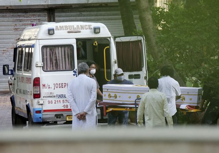 Health workers unload the dead body of Father Stan Swamy from an ambulance, outside Shivaji Park Electric Crematorium in Mumbai, Tuesday, July 6