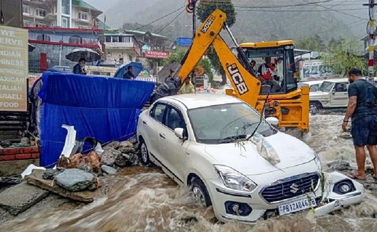 An earthmover machine attempts to remove vehicle caught in flood water