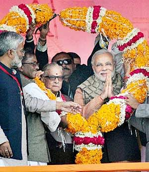 BJP PM candidate Narendra Modi is garlanded along with senior leader MM Joshi at an election campaign rally in Varanasi on Friday.