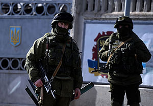 Armed men, believed to be Russian servicemen, stand guard outside an Ukrainian military base in Perevalnoye.