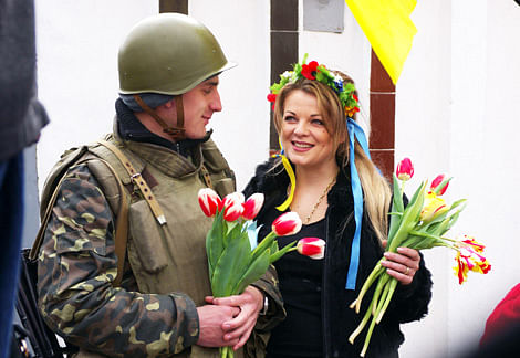 A girl presents flowers to a soldier of Ukrainian army on monday.