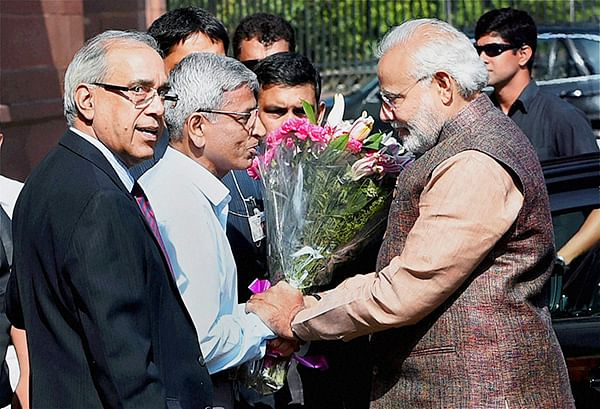 Prime Minister Narendra Modi is greeted by  officials as he arrives at South Block to take charge of the office in New Delhi on Tuesday.