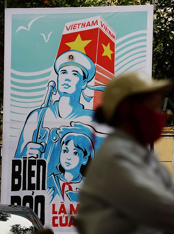 A motorcyclist rides past a propaganda billboard  featuring Vietnam's determination to defend its coastal waters and islands.