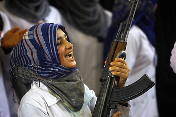 Shiite women hold weapons to show their willingness to join security forces in their fight against Jihadists.