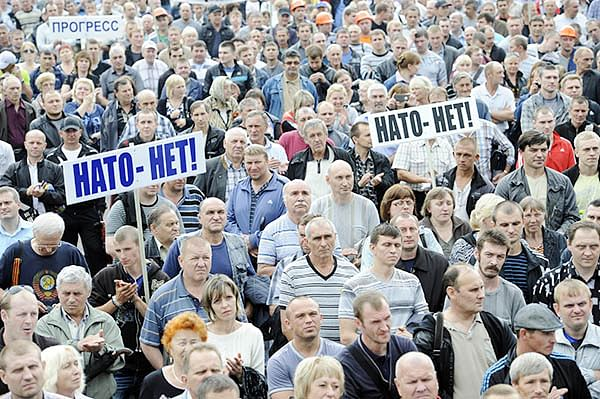 """People hold placards """"No NATO!"""" at a rally in  support of """"Donetsk People's Republic"""" in Ukraine."""