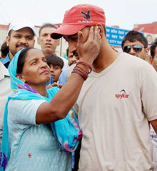 One of the workers stranded in Iraq, Vinod Kumar returns home and meets his mother in Jalandhar on Wednesday.