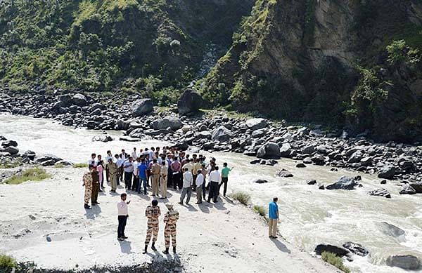 Rescue personnel gather on the banks of the Beas  River during a search operation in Kullu on Monday.