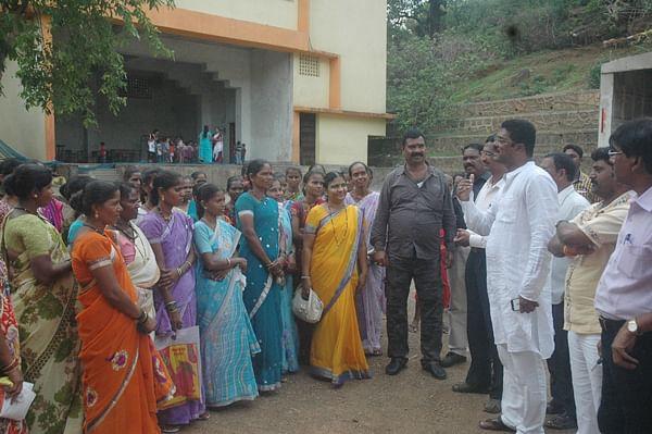 Shiv Sena legislator Pratap Sarnaik (L) interacts with parents who cannot afford private education.