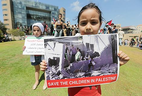 Two girls hold placards as Palestinian activists demonstrate outside the United Nations offices in Beirut .